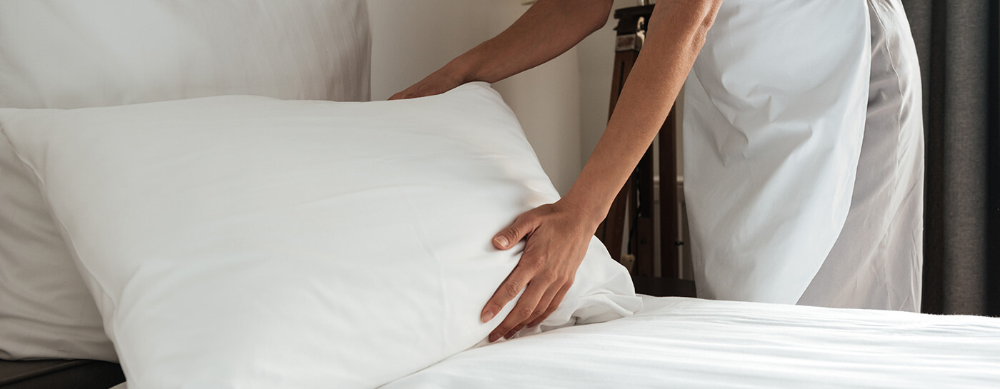 Cleaning hotel room bedding by hospitality staff